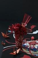 和柄の敷物の上に赤い器に赤いアレンジと折鶴 10405000325| 写真素材・ストックフォト・画像・イラスト素材|アマナイメージズ