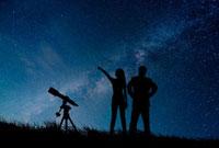 星空と望遠鏡と人物シルエット