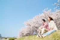 土手に座る日本人カップル 10417003008| 写真素材・ストックフォト・画像・イラスト素材|アマナイメージズ