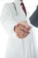 握手する医師とビジネスマンの手元