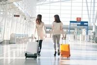 キャリーバッグをひいて歩く2人の女性の後ろ姿