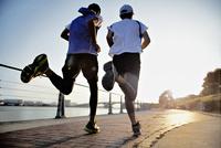 ジョギングをする2人の男性の後ろ姿