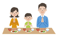 食卓で食事する家族