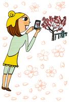 桜のイメージの中で桜の写真を撮る女性
