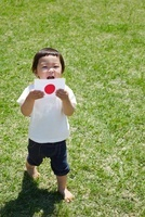 芝生の上で日本国旗を持つ子供