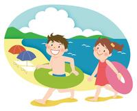 浮き輪を持って砂浜を走る二人の子供
