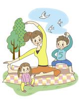 芝生の上でストレッチする家族