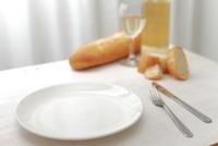 食卓の洋食器とパンと白ワイン