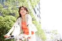 街を自転車で走るビジネスウーマン