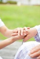 車椅子のシニア女性の手を握る女性看護師の手元