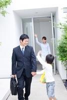 母親に見送られて手をつないで玄関を出る父親と男の子