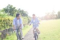 芝生の公園をサイクリングする夫婦