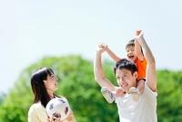 公園を歩く3人家族