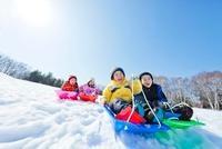 雪の公園でソリ遊びをする子供たち