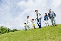 公園を手をつないで歩く3世代