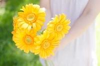 オレンジのガーベラを持つ女性のイメージ 10568000264| 写真素材・ストックフォト・画像・イラスト素材|アマナイメージズ