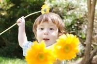 オレンジのガーベラで遊ぶハーフの男の子 10568000266| 写真素材・ストックフォト・画像・イラスト素材|アマナイメージズ