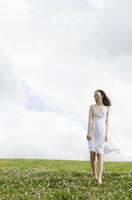 白いワンピースを着てシロツメクサの上を歩くハーフの少女