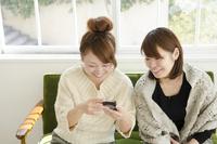 スマートフォンの画面を見て笑う女性2人
