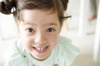 机の下で笑うハーフの女の子 10568000854| 写真素材・ストックフォト・画像・イラスト素材|アマナイメージズ