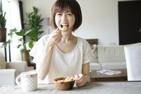 フルーツサラダを笑顔で食べる女性