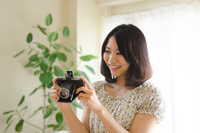 クラシックカメラを見ている笑顔の女性