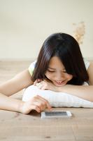 床に寝そべってスマートフォンを操作する女性