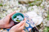 お茶の入った湯のみと女性の手