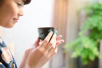 お茶の入った湯のみを持つ着物姿の女性