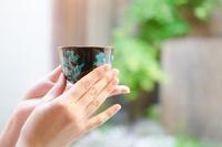 お茶の入った湯のみを持つ着物姿の女性の手