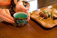 机にある和菓子と湯のみに添えられた着物姿の女性の手