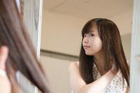 鏡の前で髪をセットする女性