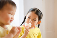おせんべいを食べている姉妹 10568002001| 写真素材・ストックフォト・画像・イラスト素材|アマナイメージズ