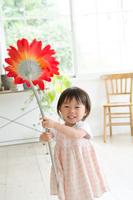 部屋の中で大きなお花を持っている女の子