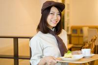 制服を着てカフェで働く女性