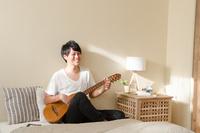 ベッドの上でギターを弾く男性