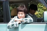 車から乗り出して笑う女性 10568002861| 写真素材・ストックフォト・画像・イラスト素材|アマナイメージズ