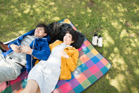 ピクニックマットの上に寝転がる男女