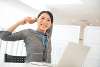 ノートパソコンの前でストレッチをしている女性