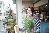 お花の鉢を持って笑っている女性