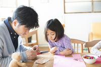 テーブルで遊んでいる女の子とお父さん