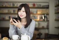 カフェでスマホを見ている女性 10568003743| 写真素材・ストックフォト・画像・イラスト素材|アマナイメージズ