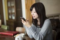 スマホを触っている女性 10568003744| 写真素材・ストックフォト・画像・イラスト素材|アマナイメージズ