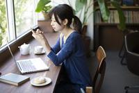 カフェでスマホを触っている女性 10568003809| 写真素材・ストックフォト・画像・イラスト素材|アマナイメージズ