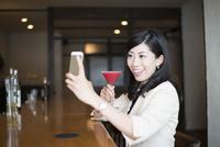 カクテルを片手に自撮りをする女性 10568003881| 写真素材・ストックフォト・画像・イラスト素材|アマナイメージズ