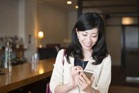バーでスマホを触っている女性