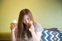 部屋でポテトチップを食べている女性 10568004168| 写真素材・ストックフォト・画像・イラスト素材|アマナイメージズ