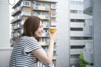 ベランダでビールを飲んでいる女性 10568004192| 写真素材・ストックフォト・画像・イラスト素材|アマナイメージズ