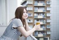 ベランダでビールを持っている女性 10568004193| 写真素材・ストックフォト・画像・イラスト素材|アマナイメージズ