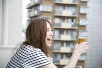 ベランダでビールを持っている女性
